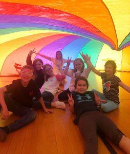 7 children under a rainbow tent