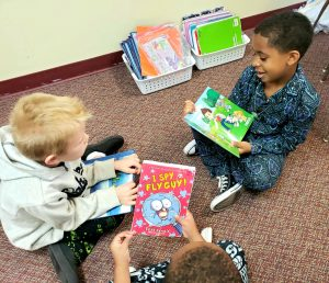 3 students reading books in their pajamas.