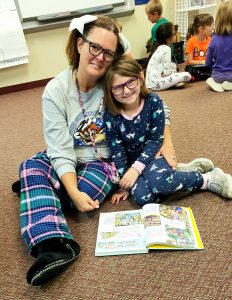 A teacher and student reading a book in their pajamas.