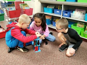 Students building with blocks in a classroom floor