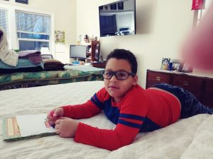 A student reading in his pajamas
