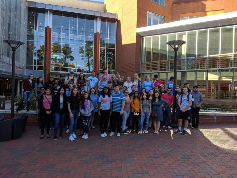 Early college students group in front of red brick building