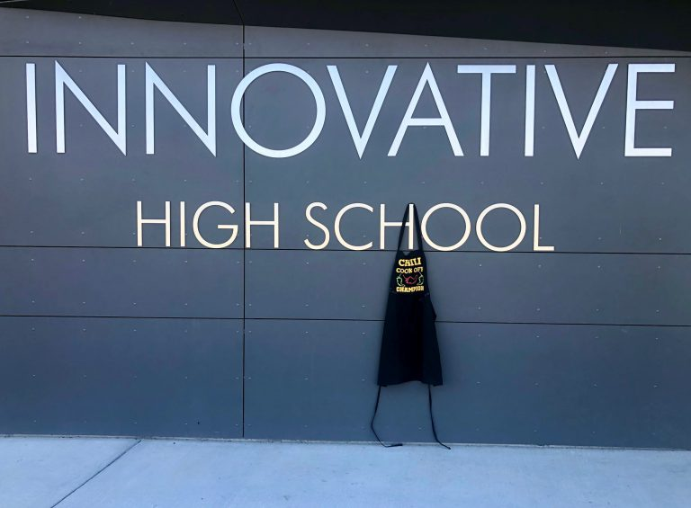 black apron hanging on school letters