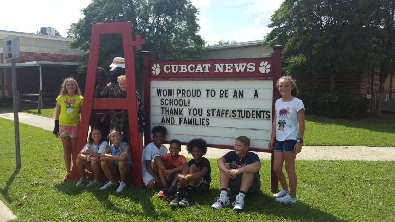 Students standing in front of school marquee sign.