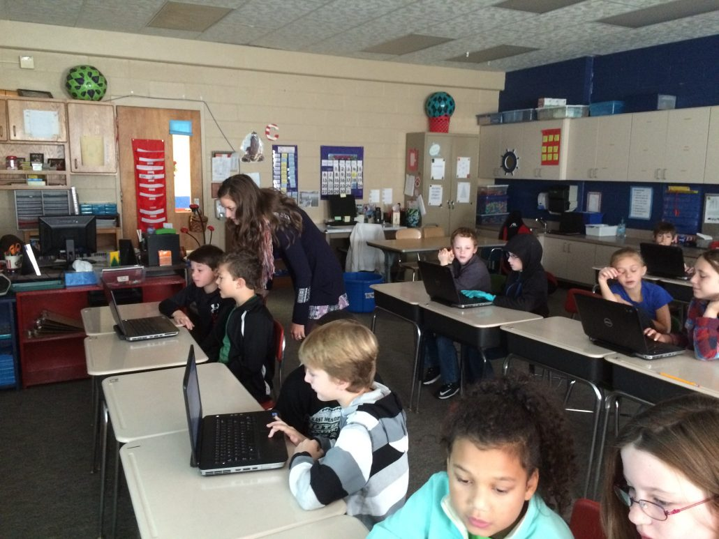 Entire classroom of students working in pairs on coding activities