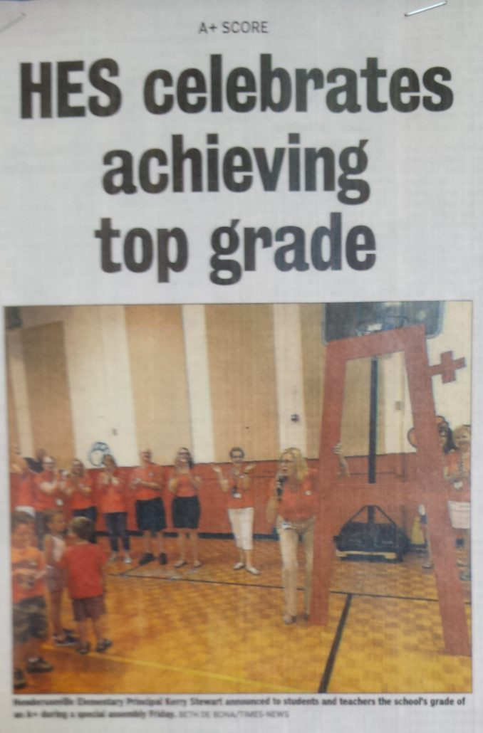 Newspaper article with headline: HES celebrates achieving top grade