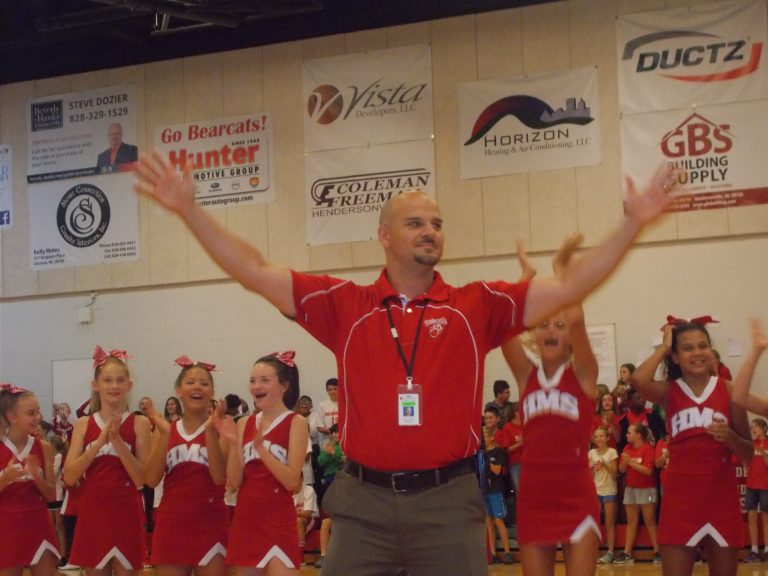 Mr. Manuel With arms raised and students cheering behind him