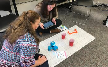 Two teachers working with Dash using cups, a grid mat, and an iPad
