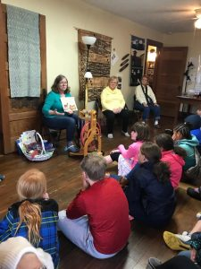 HWFA members read a story to students.