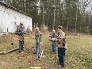 4 men work on fixing barbed wire fence.