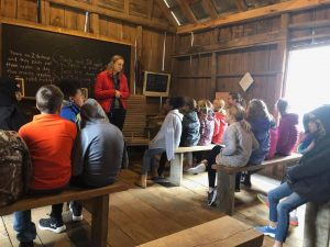 Students sit in the replica one-room schoolhouse.