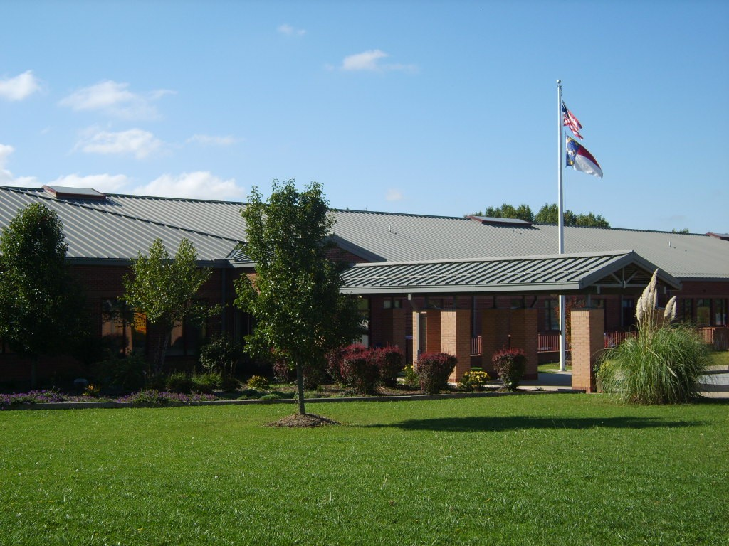 A photo of Glenn C. Marlow Elementary School from the outside. The flag pole is visible with the American flag raised.