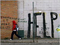 HELP Graffiti on wall. Youth in red hoodie walking past the wall.