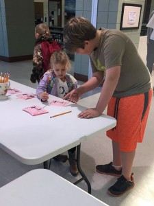 5th grader helps student fill out Valentine