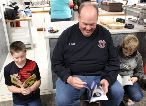 Students reading with a firefighter