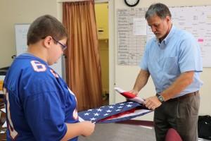 Principal and student fold flag