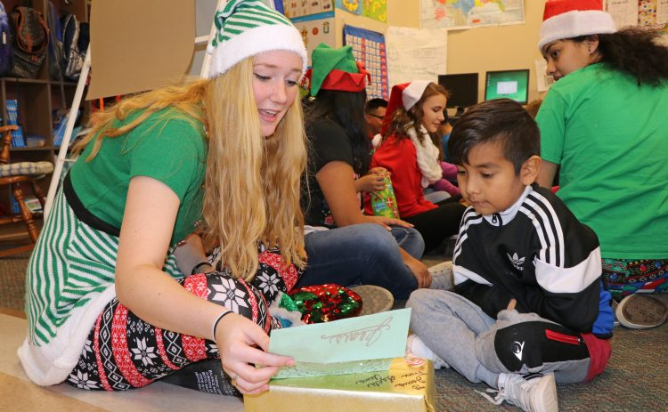 High school student opens presents with 1st-grader