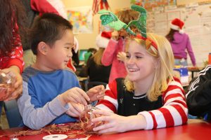 High school student helps 1st-grader make ornament