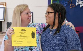 Student receives leadership award from teacher.