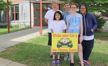 "Students with a ""Make Your Car a No Phone Zone"" sign."