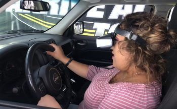 Student with virtual reality goggles does a driving simulation.
