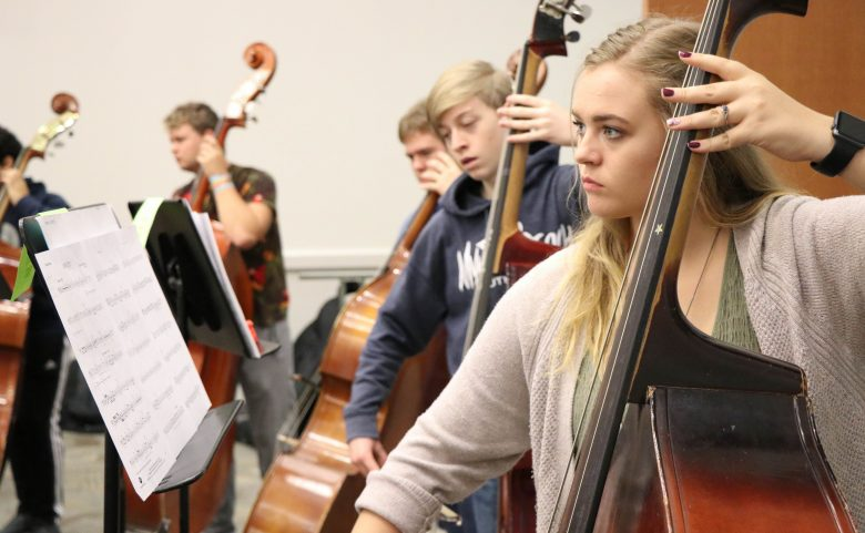 Students playing upright basses