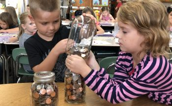 Students transfer change to a mason jar.