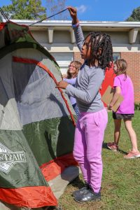 Student assembling a camping tent.