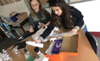 Students pack shoeboxes with donations