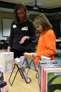 Library staffmember helps student choose book