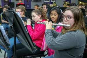 elementary student watches high school student play flute