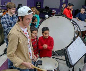elementary boys watch high schooler play drums