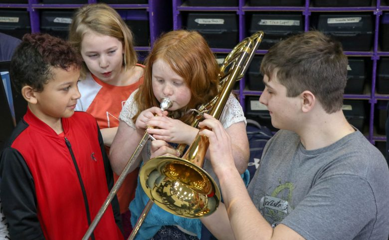 high school student holds trombone for elementary student to play