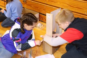 2 students building with plywood