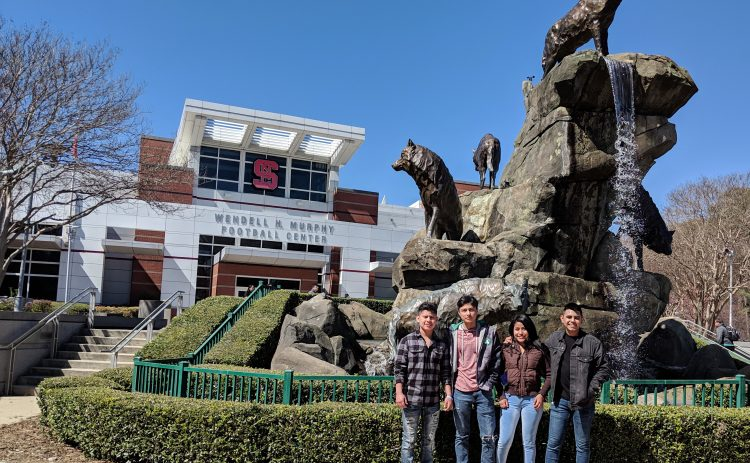 4 students in front of fountain