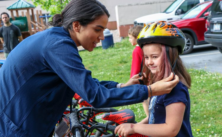 adult adjusting childs bike helmet