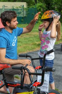 adult helps child with bike helmet