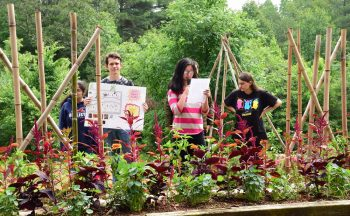 Four students presenting in their garden