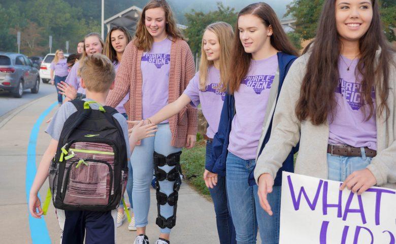 6 high school girls high fiving an elementary student
