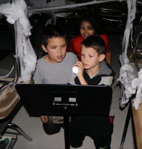 3 boys using flashlight to read