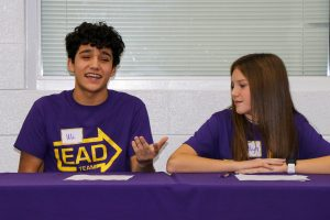 2 students at purple table, smiling