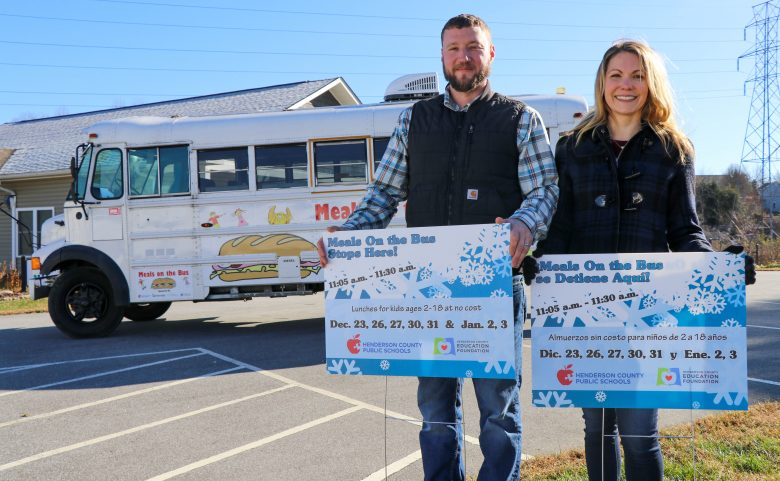2 people standing outside with signs and bus