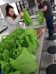 2 volunteers packing bags of food