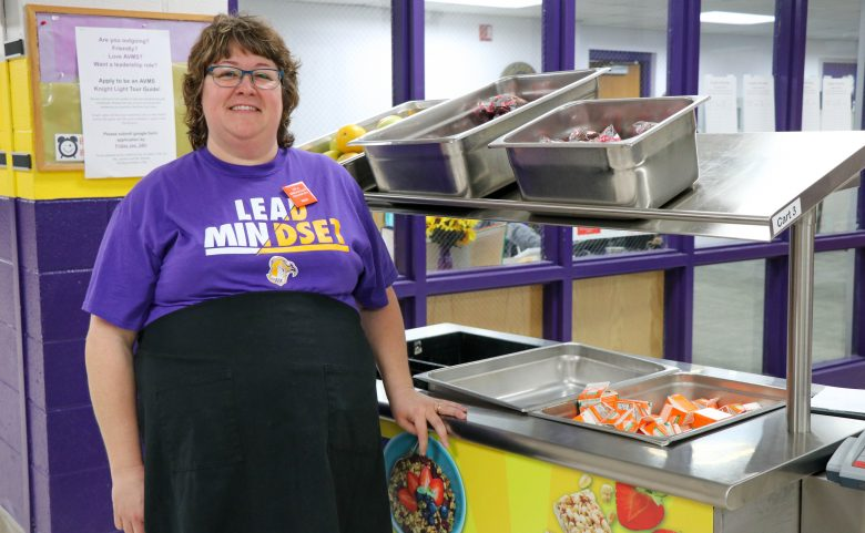 woman in apron standing in front of food cart
