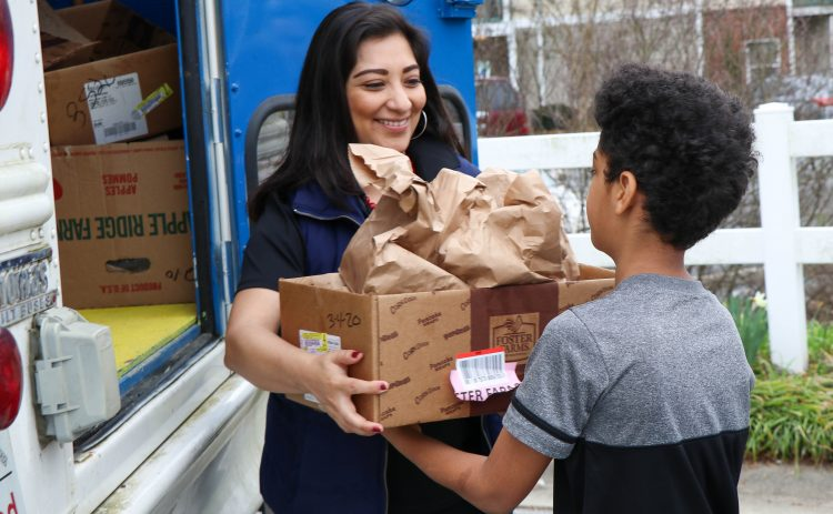 woman handing box of food to child