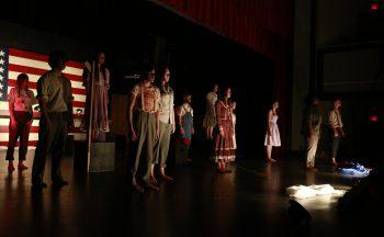 12 high school students on dark stage