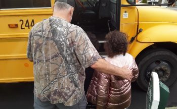 man and child approaching school bus
