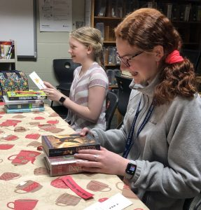 two middle school girls smiling as they look through books