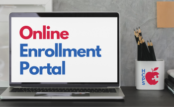 """computer screen on desk with """"Online Enrollment Portal"""" on screen"""