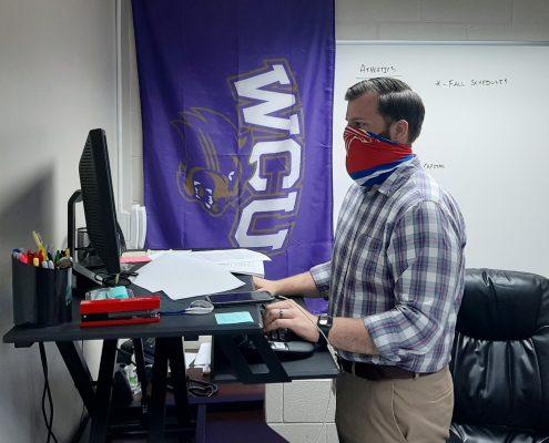 teacher at standing desk wearing mask
